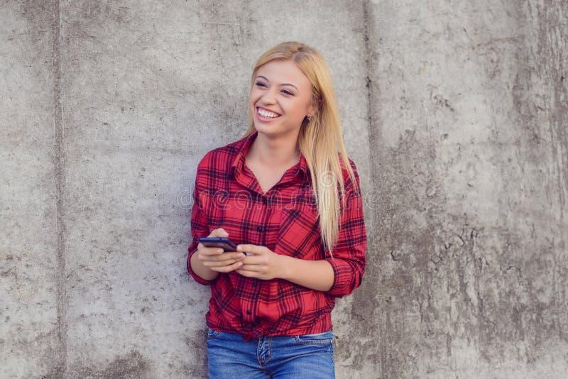 Lycklig le kvinna som använder hennes smartphone för att skriva med vännen arkivfoto