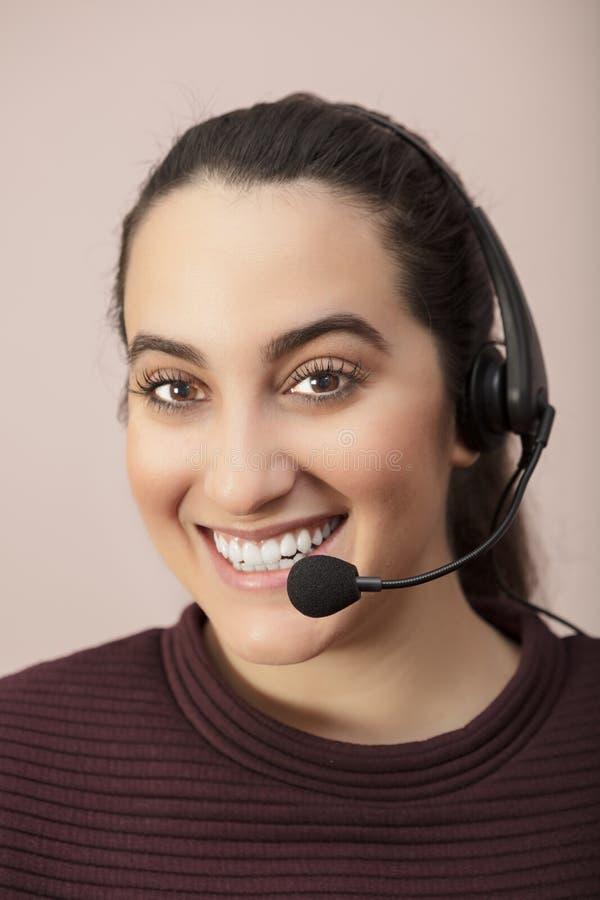 Lycklig le kvinna som bär en hörlurar med mikrofon fotografering för bildbyråer