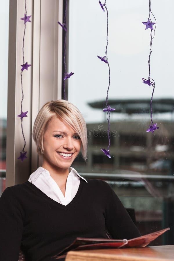 Lycklig le kvinna som beställer i en kafeteria arkivfoton