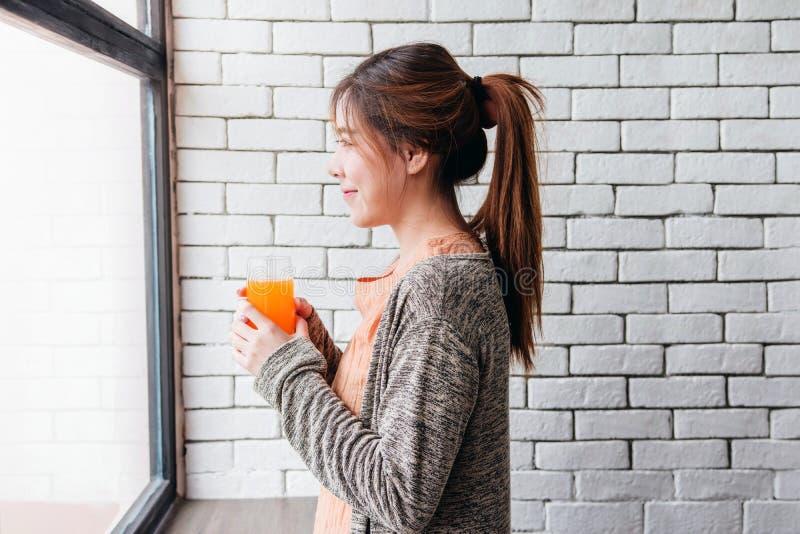 Lycklig le kvinna som kopplar av i hemtrevligt hus och innehav en glass nolla arkivbild