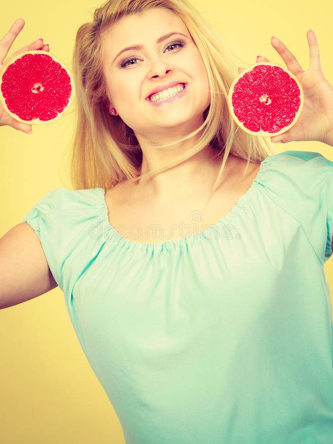Lycklig le kvinna som rymmer den r?da grapefrukten royaltyfria foton
