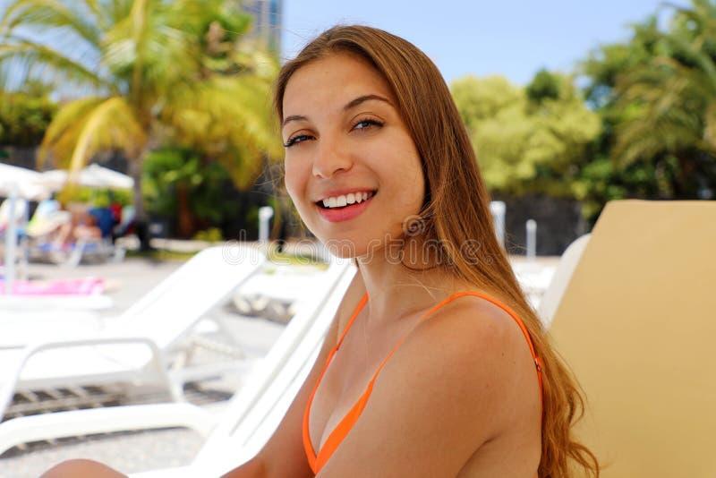 Lycklig le kvinna som sitter på solstol i tropisk pöl Skratta flickan som tycker om solen på ferier på stund för hotellsemesteror royaltyfria bilder