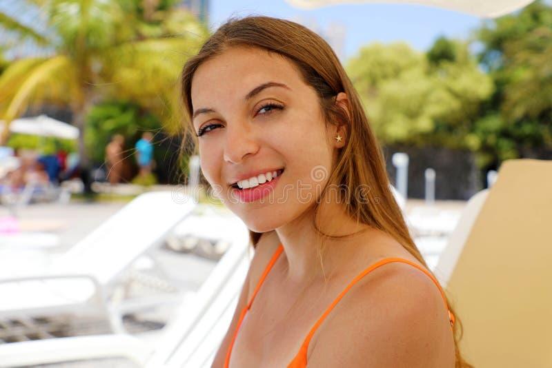 Lycklig le kvinna som sitter på solstol i tropisk pöl Skratta flickan som tycker om solen på ferier på stund för hotellsemesteror fotografering för bildbyråer
