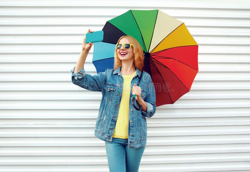 Lycklig le kvinna som tar selfiebilden vid telefonen med det färgrika paraplyet i stad på den vita väggen fotografering för bildbyråer
