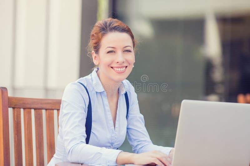 Lycklig le kvinna som utanför arbetar på datorbärbara datorn arkivfoto