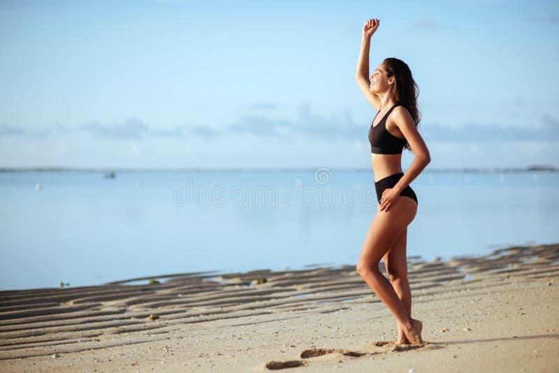 Lycklig le kvinnabanhoppning p? stranden royaltyfria bilder