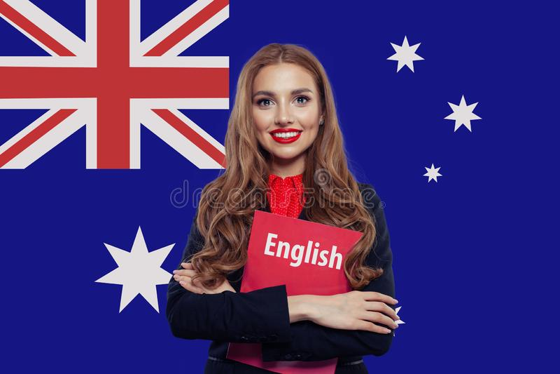 Lycklig le kvinnastudent med boken mot australisk flaggabakgrund Lopp och utbildning i Australien royaltyfria foton