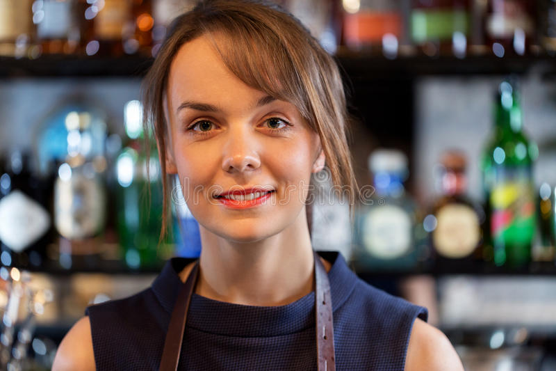 Lycklig le kvinnlig bartender eller kvinna på coctailstången arkivfoton