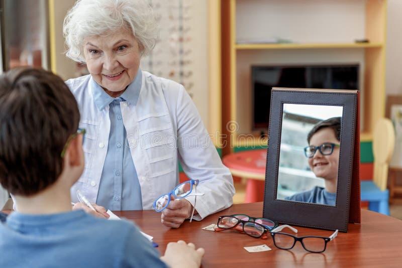 Lycklig le kvinnlig gammal ögonläkare som talar med patienten royaltyfri fotografi