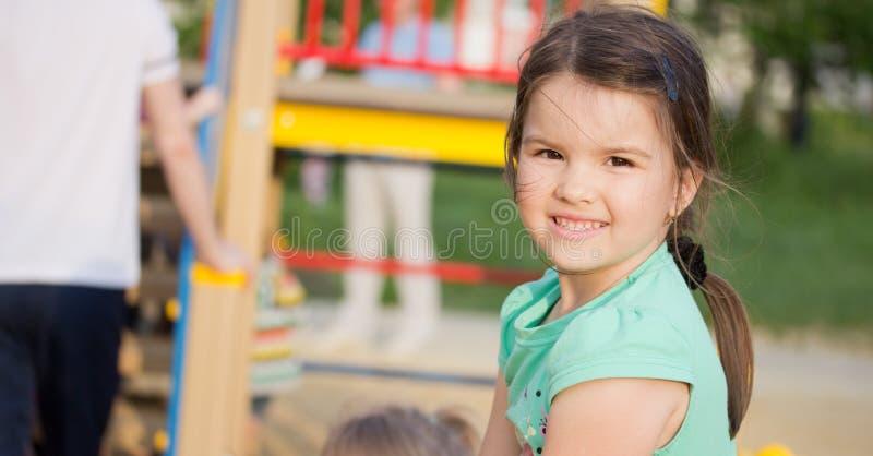 Lycklig le liten flicka på lekplats royaltyfri foto