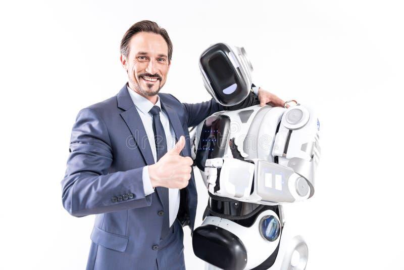 Lycklig le manlig person som omfamnar cyborgen royaltyfri fotografi