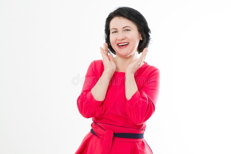 Lycklig le mellersta ålderkvinna i den röda klänningen som isoleras på vit bakgrund Smink- och modeskönhetbegrepp kopiera avstånd royaltyfri bild