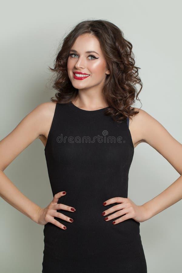 Lycklig le modellkvinna i svart klänninganseende royaltyfri foto