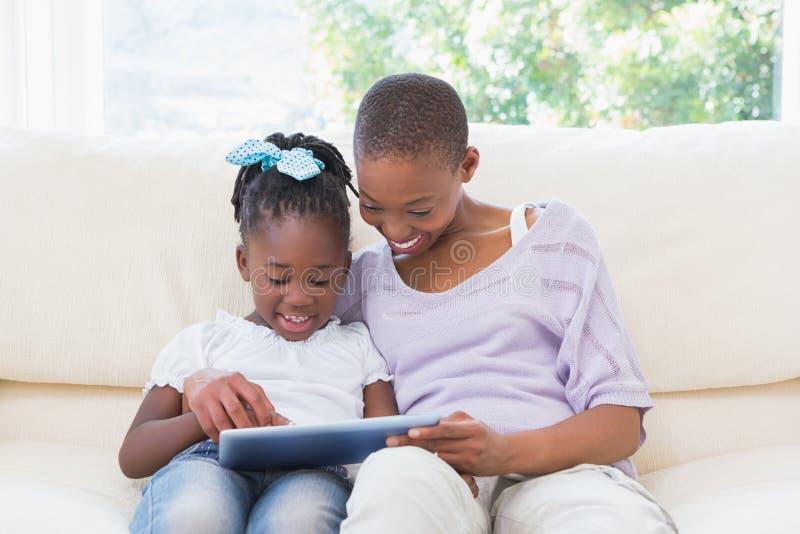 Lycklig le moder som använder minnestavlan med hennes dotter på soffan royaltyfri fotografi