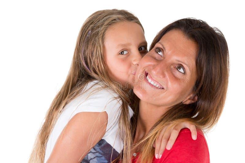 Lycklig le moder som kramar kyssa dottern för litet barn på en vit bakgrund arkivbild