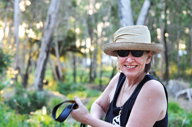 Lycklig le mogen kvinna i hatt på att fotvandra för skogslinga royaltyfri foto
