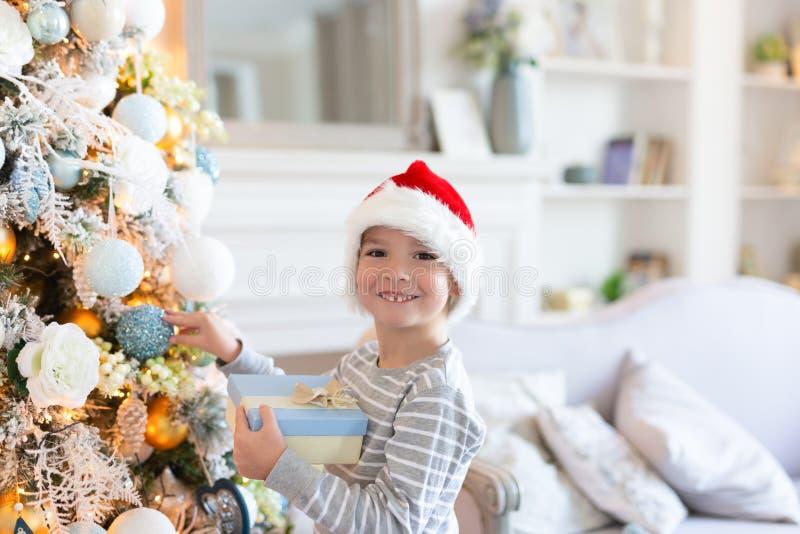 Lycklig le pojke i santa hattanseende nära julträd med gåvan julen dekorerar nya home idéer för garnering till isolerat nytt vitt arkivfoton