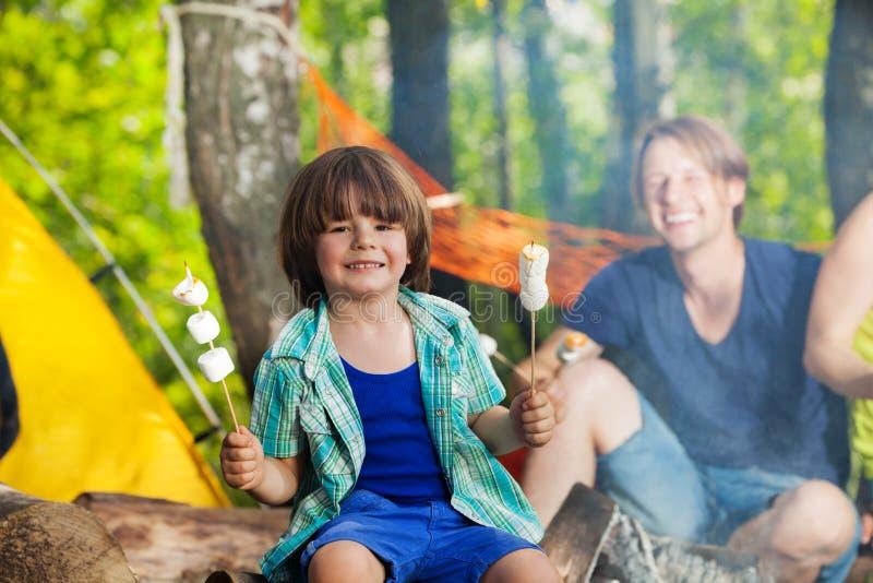 Lycklig le pojke som äter marshmallower på campingplatsen royaltyfria bilder