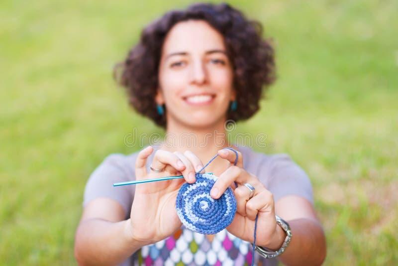 Lycklig le potholder för kvinnadanandevirkning utomhus arkivbild