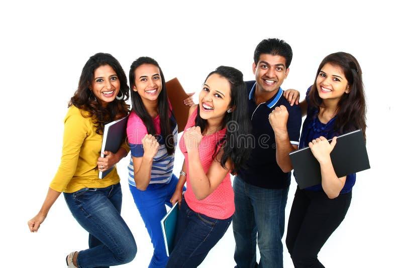 Lycklig le stående av den unga indiern/asiatet Isolerat på den vita backgroen arkivfoto