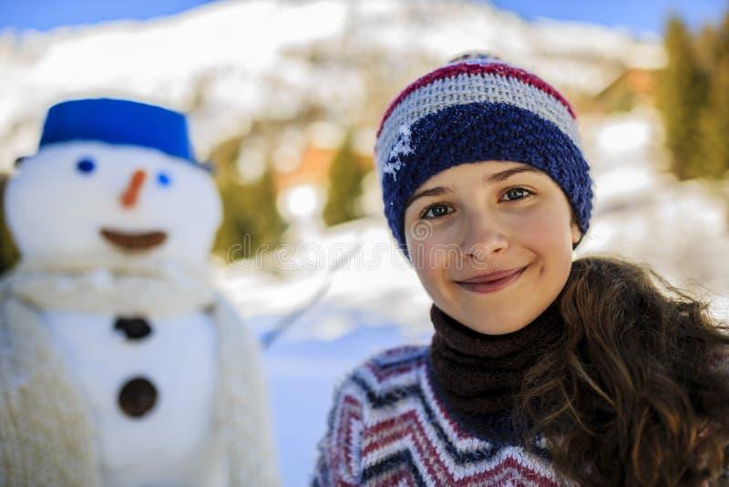 Lycklig le tonårs- flicka som spelar med en snögubbe royaltyfria foton