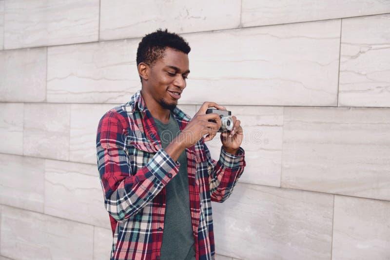 Lycklig le ung afrikansk man för stående med tappningfilmkameran som tar bilden som går på stadsgatan över den gråa tegelstenvägg royaltyfri bild