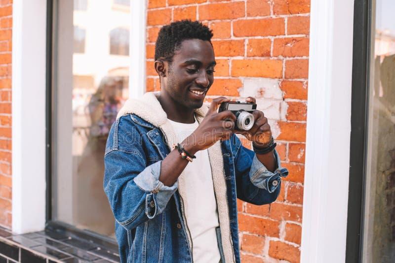 Lycklig le ung afrikansk man för stående med tappningfilmkameran som tar bilden som går på stadsgatan över tegelstenväggen royaltyfri fotografi