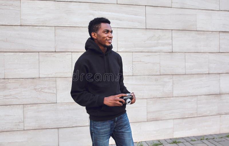Lycklig le ung afrikansk man med tappningfilmkameran i svart hoodie som går på stadsgatan royaltyfria bilder