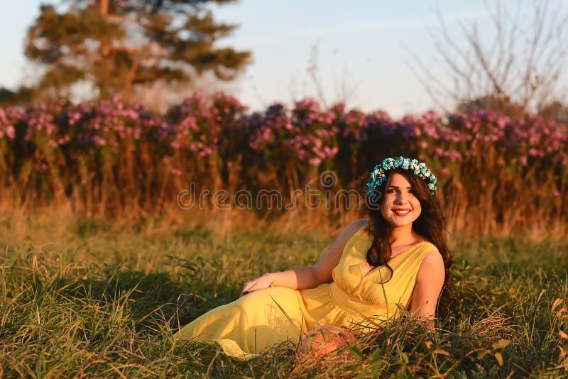 Lycklig le ung flicka, attraktiv kvinna som bär den gula klänningen som går i blommafältet Innehåll lutning- och urklippmaskering royaltyfri bild