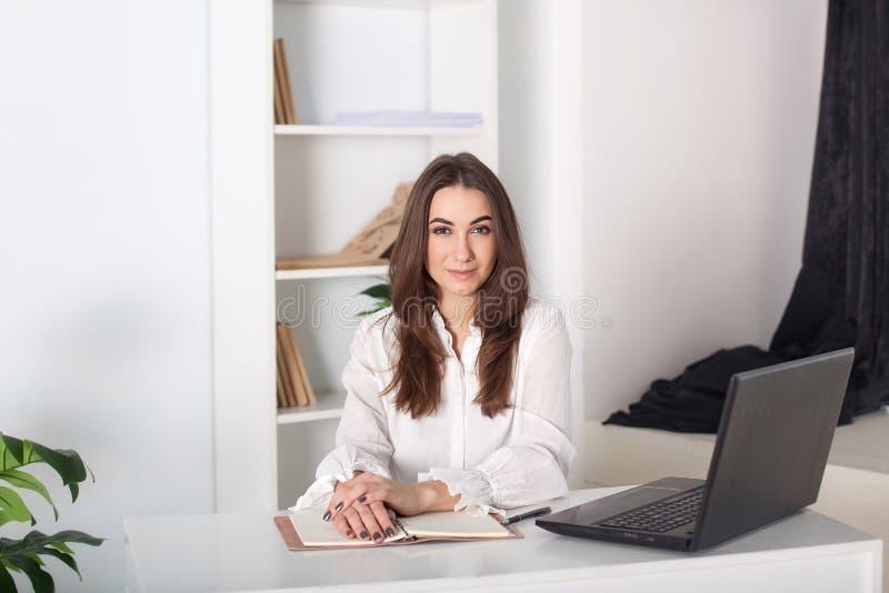 Lycklig le ung flicka som arbetar i kontoret Närbildstående av en kontorsarbetare Positiv ung chef som arbetar på affär arkivbild