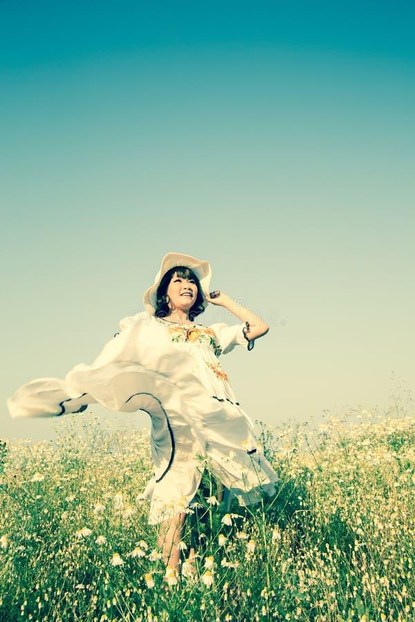 Lycklig le ung flicka som bär en klänning för landsstil med hatten fotografering för bildbyråer