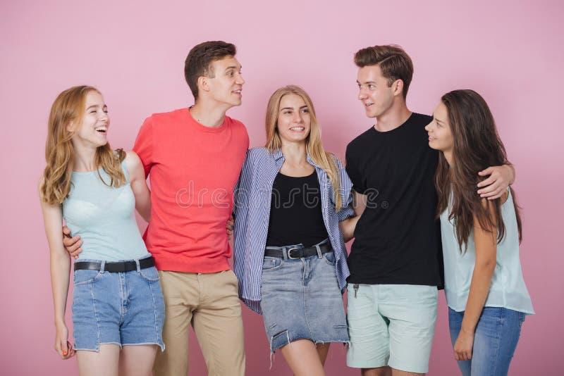 Lycklig le ung grupp av vänner som står som talar och skrattar tillsammans Bästa vän arkivbilder