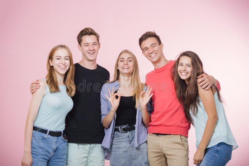Lycklig le ung grupp av vänner som står som talar och skrattar tillsammans Bästa vän royaltyfri foto