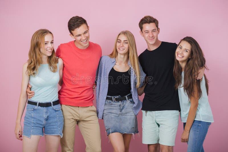 Lycklig le ung grupp av vänner som står som talar och skrattar tillsammans Bästa vän arkivbild