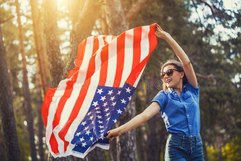 Lycklig le ung kvinna med den nationella amerikanska flaggan utomhus royaltyfri fotografi