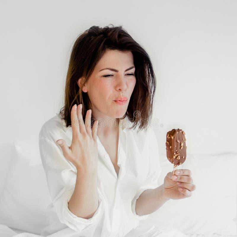 Lycklig le ung kvinna som äter glass i ett sovrum Beautif royaltyfria foton