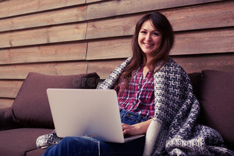 Lycklig le ung kvinna som håller ögonen på och arbetar på datoren på ho royaltyfria foton