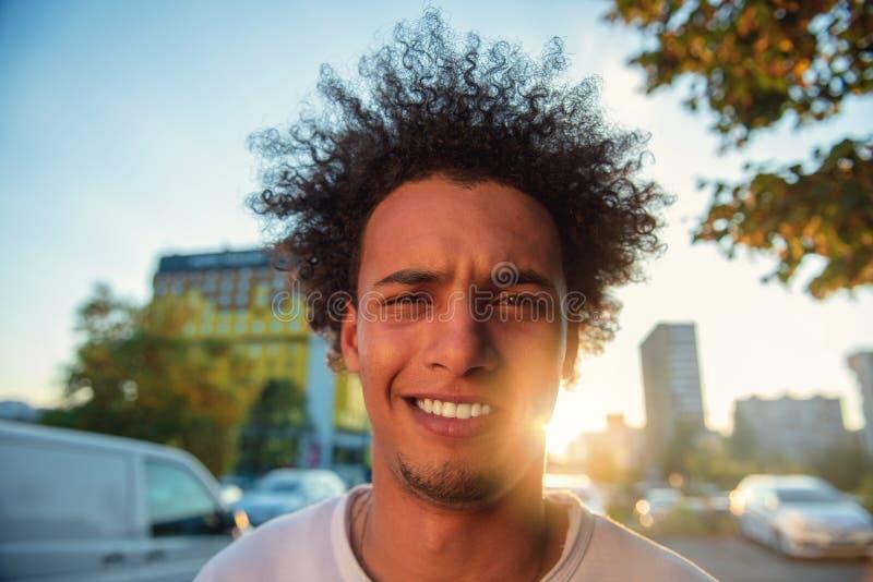 Lycklig le ung man f?r stads- hipster som anv?nder den smarta telefonen Afrikansk amerikanton?ring som rymmer den mobila smartpho arkivfoton