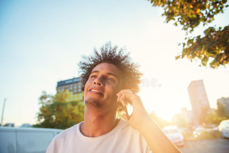 Lycklig le ung man f?r stads- hipster som anv?nder den smarta telefonen Afrikansk amerikanton?ring som rymmer den mobila smartpho royaltyfri bild
