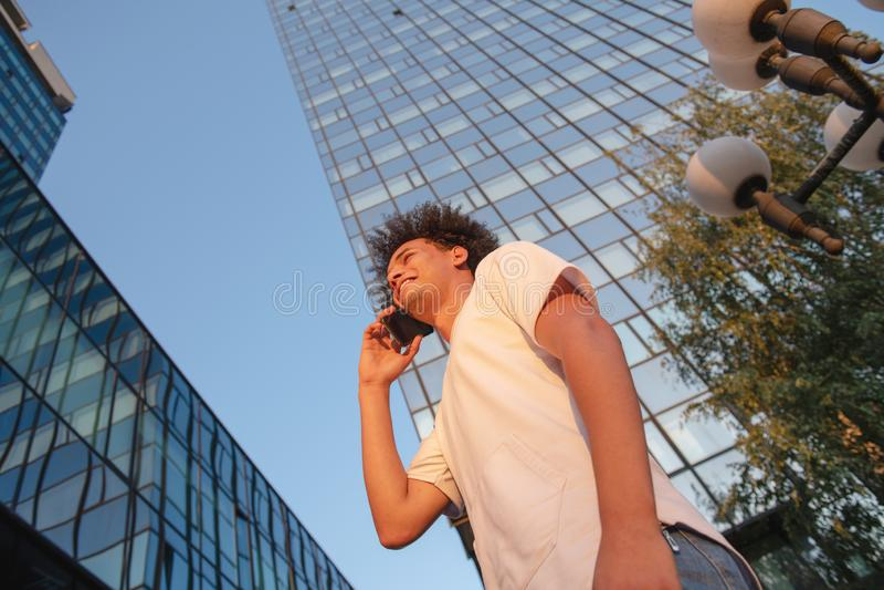 Lycklig le ung man f?r stads- hipster som anv?nder den smarta telefonen Afrikansk amerikanton?ring som rymmer den mobila smartpho royaltyfria bilder
