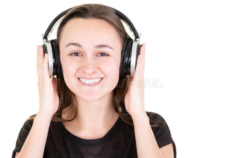 Lycklig le ung nätt kvinna med hörlurar som tycker om musikhänder på discjockeyhörlurar med mikrofon arkivbild