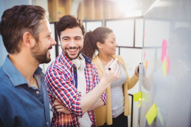 Lycklig ledare med kollegor som står vid whiteboard på det idérika kontoret royaltyfria foton