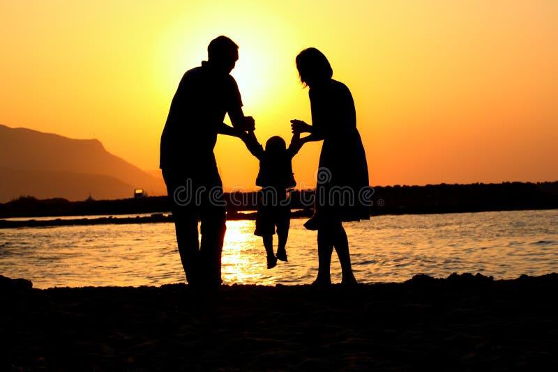 lycklig leka silhouette tre för familj royaltyfria bilder