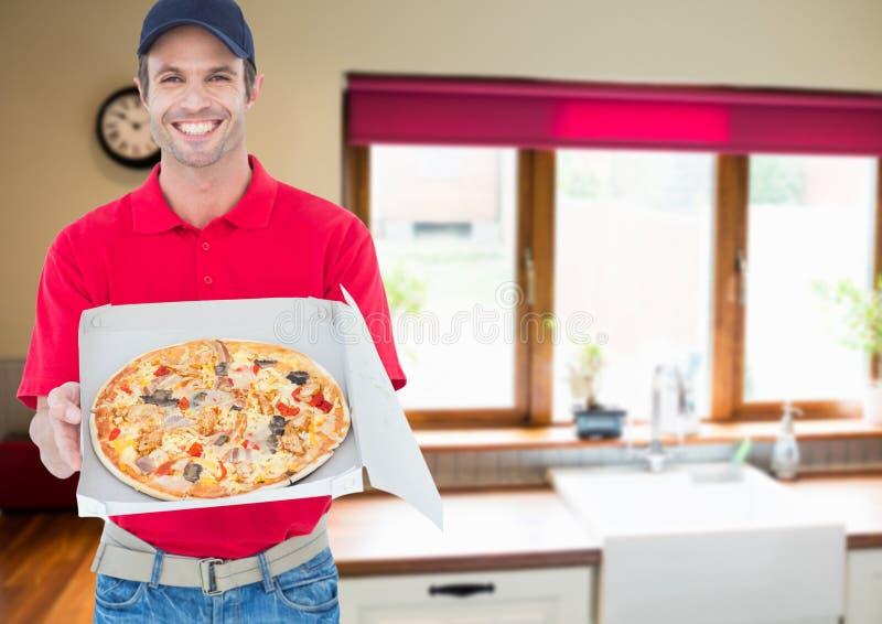 Lycklig leverans som sår pizza i köket arkivfoton