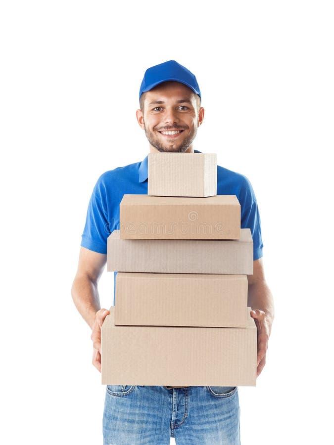 Lycklig leveransman i blå enhetlig innehavhög av kartongen royaltyfria foton
