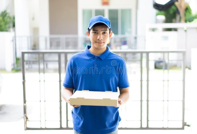 Lycklig leveransperson i blått enhetligt hållande pizzaaskanseende royaltyfri bild