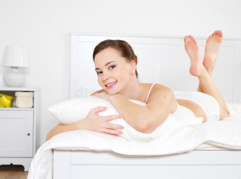 lycklig liggande avslappnande kvinna för härligt underlag royaltyfri foto