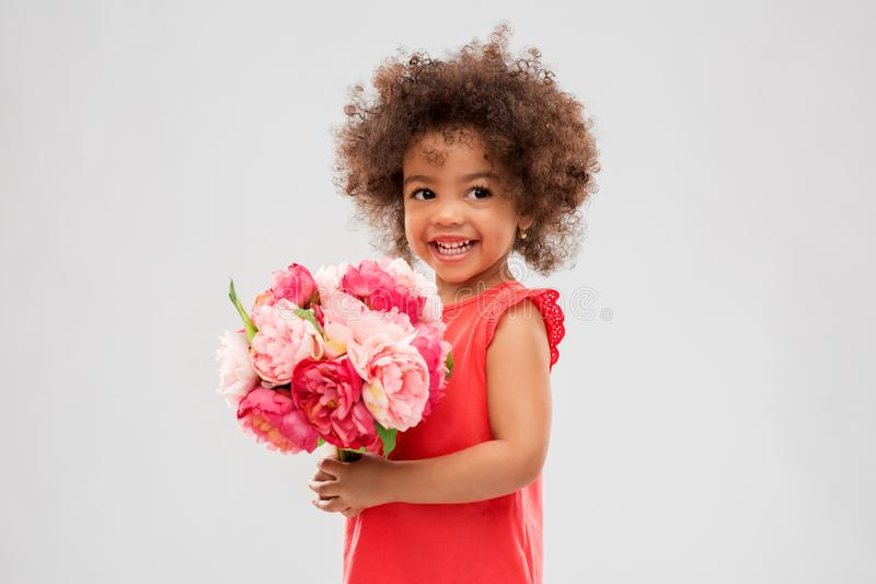 Lycklig liten afrikansk amerikanflicka med blommor royaltyfri bild