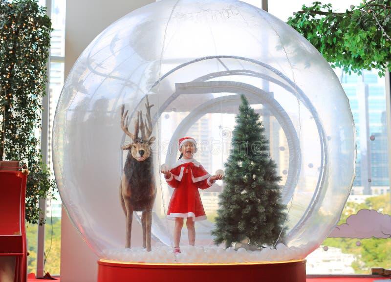 Lycklig liten asiatisk barnflicka i den santa dräktklänningen som spelar i stort vintersnöjordklot med renen på jultid glad xmas fotografering för bildbyråer