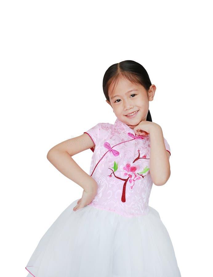 Lycklig liten asiatisk barnflicka som bär den kinesiska klänningen för rosa tradition för kinesisk beröm för nytt år som isoleras royaltyfri bild